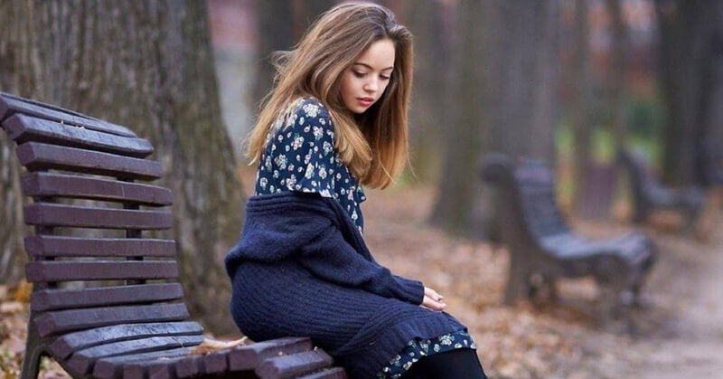 Girl sitting in park bench waiting and thinking about her ex